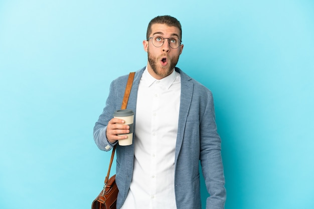 파란색 벽을 찾고 놀란 표정으로 고립 된 젊은 백인 사업가