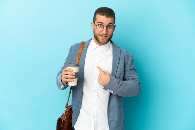 놀라운 표정으로 파란색 벽에 고립 된 젊은 백인 사업가
