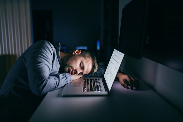 Young caucasian businessman sleeping in the office late at night.