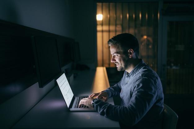 Молодой кавказский бизнесмен, набрав на ноутбуке, сидя в офисе поздно ночью.