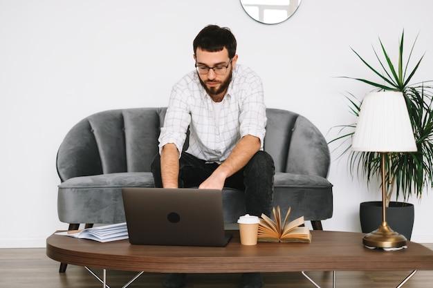 젊은 백인 사업가 집에서 작업, 프리랜서 작업, 랩톱 컴퓨터를 사용합니다.