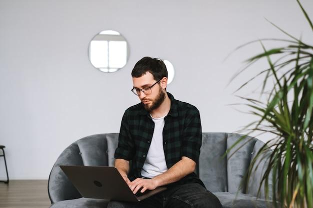 若い白人ビジネスマンは自宅で仕事、フリーランスの仕事、ラップトップコンピューターを使用しています。