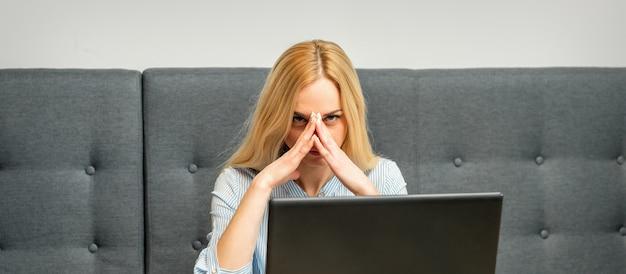 Молодая кавказская бизнесвумен устала от работы, сидя за столом в кафе