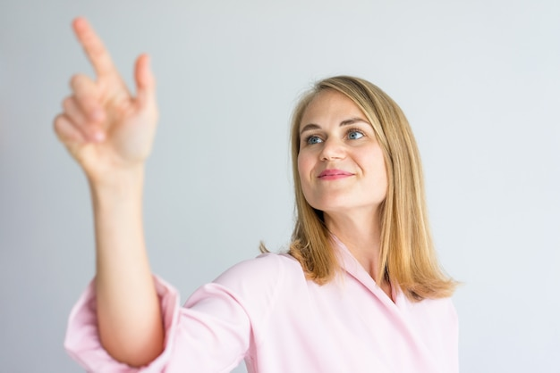 Young caucasian businesswoman wearing pink blouse using glassy board at presentation