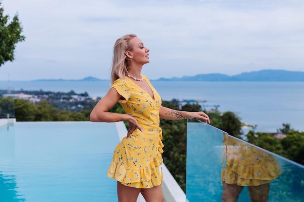 여름 노란 드레스와 바다 쉘 목걸이를 입고 밝은 저녁 화장과 젊은 백인 진정 행복 예쁜 여자