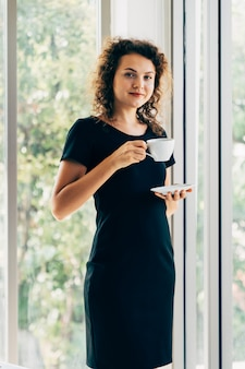 立っている間笑顔若い白人カジュアルなビジネス女性がオフィスの窓の横にあるコーヒーを飲んでリラックスします。