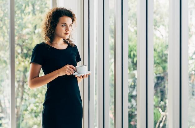 ホームオフィスの窓の横にコーヒーを飲みながら立っている若い白人カジュアルビジネス女性立っている思考