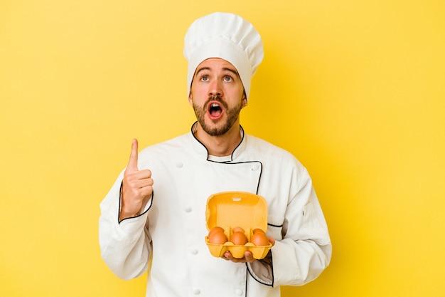 열린 된 입으로 거꾸로 가리키는 노란색 배경에 고립 된 계란을 들고 젊은 백인 요리사 남자.