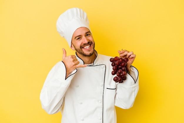 손가락으로 휴대 전화 제스처를 보여주는 노란색 배경에 고립 된 포도 들고 젊은 백인 요리사 남자.