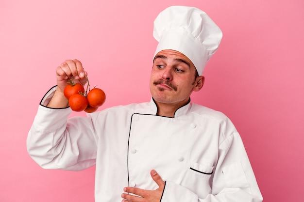 분홍색 배경에 고립 토마토를 들고 젊은 백인 요리사 남자