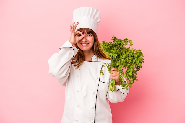 Young caucasian chef woman holding parsley isolated on pink background excited keeping ok gesture on eye.