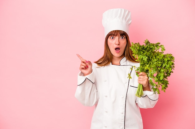 Young caucasian chef woman holding parsley isolated on pink background pointing to the side