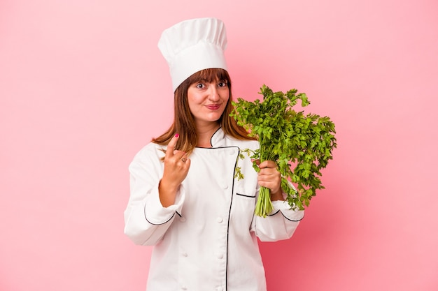 Young caucasian chef woman holding parsley isolated on pink background pointing with finger at you as if inviting come closer.