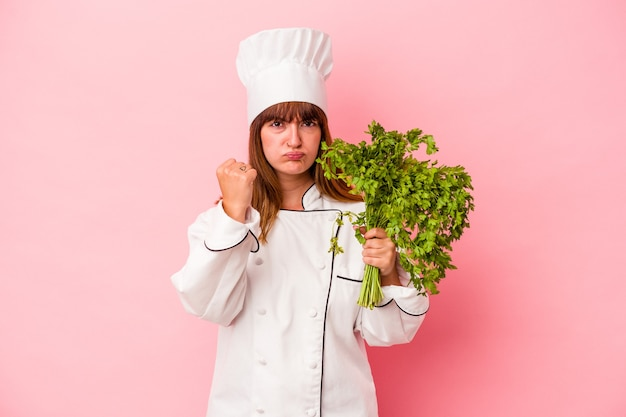 Young caucasian chef woman holding parsley isolated on pink background showing fist to camera, aggressive facial expression.
