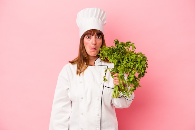 Young caucasian chef woman holding parsley isolated on pink background shrugs shoulders and open eyes confused.