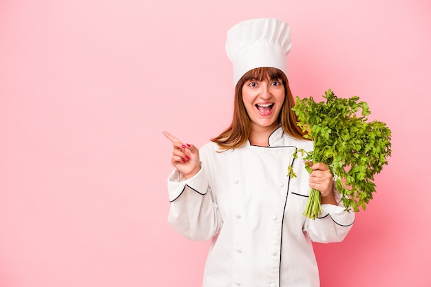 Young caucasian chef woman holding parsley isolated on pink background smiling and pointing aside, showing something at blank space.