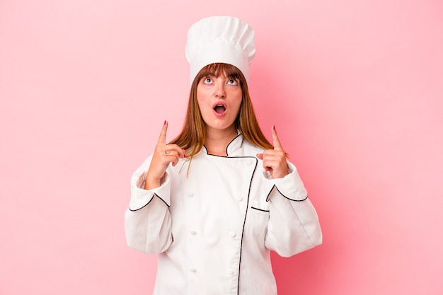 Young caucasian chef woman isolated on pink background pointing upside with opened mouth.