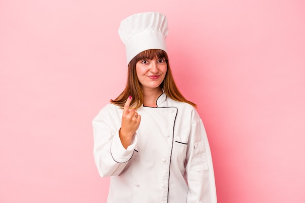 Young caucasian chef woman isolated on pink background pointing with finger at you as if inviting come closer.