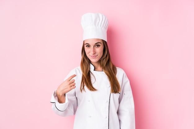 젊은 백인 요리사 여자가 가까이 와서 초대하는 것처럼 당신 손가락으로 가리키는 격리.