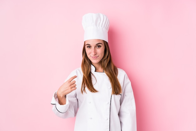 Young caucasian chef woman isolated pointing with finger at you as if inviting come closer.