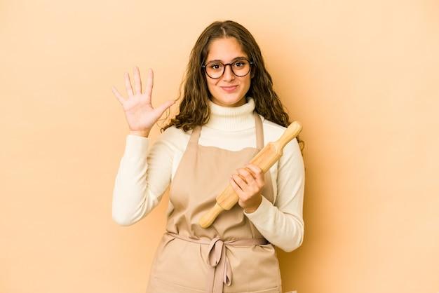 젊은 백인 요리사 여자 절연 손가락으로 5 번을 보여주는 명랑 웃 고.