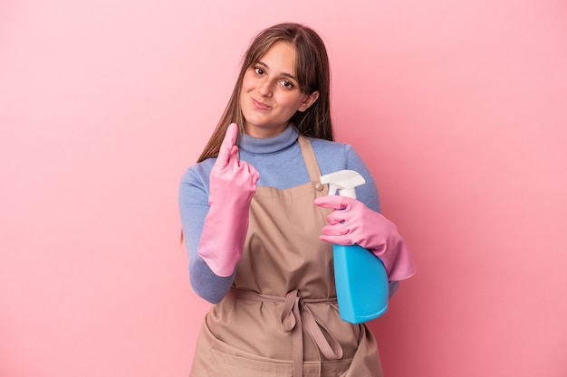 Young caucasian cleaner woman holding spray isolated on pink background pointing with finger at you as if inviting come closer.