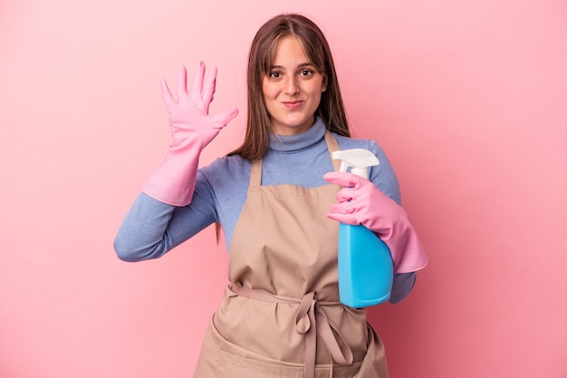 Young caucasian cleaner woman holding spray isolated on pink background smiling cheerful showing number five with fingers.