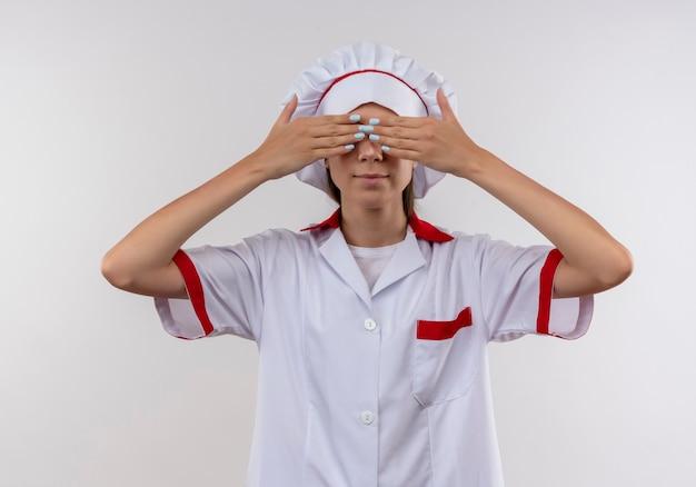 La giovane ragazza caucasica del cuoco in uniforme del cuoco unico chiude gli occhi con le mani su bianco con lo spazio della copia
