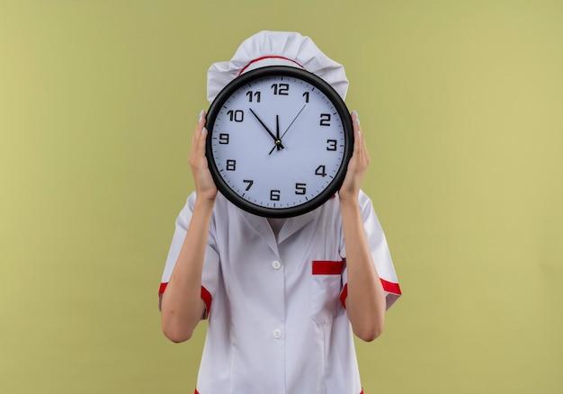 シェフの制服を着た若い白人料理人の女の子は、コピースペースで緑の時計で顔を閉じます