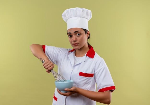 요리사 유니폼에 젊은 백인 요리사 소녀는 그릇을 보유하고 복사 공간이 녹색 배경에 고립 털