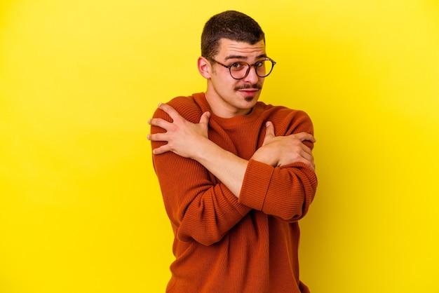 노란색 배경에 고립 된 젊은 백인 멋진 남자 포옹, 평온하고 행복 하 게 웃 고.