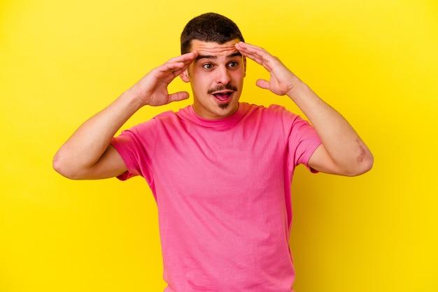 즐거운 놀라움을 받고 흥분하고 손을 올리는 노란색 벽에 고립 된 젊은 백인 멋진 남자