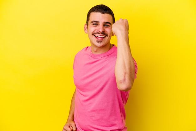 평온하고 흥분 노란색 응원에 젊은 백인 멋진 남자. 승리 개념.