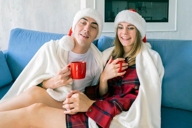 Young caucasian couple drinking hot tea or cocoa from red cups while sitting at home on the sofa wearing santa hats and pajamas wrapped in a white blanket