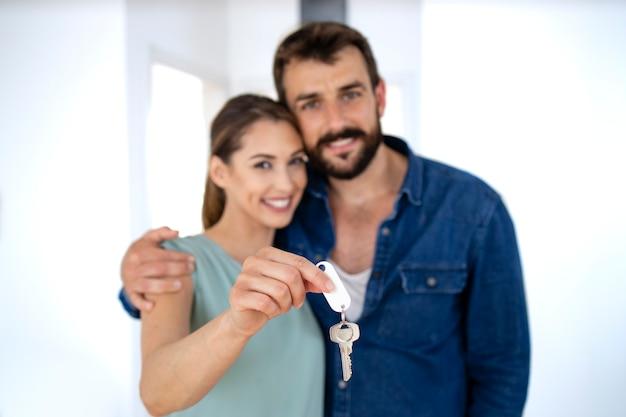 젊은 백인 부부는 새 집의 열쇠를 보여주면서 행복감을 느낍니다.