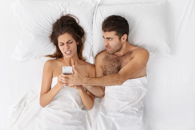 Young caucasian couple fighting in bed: unshaven man trying to snatch mobile phone from his wife's hands