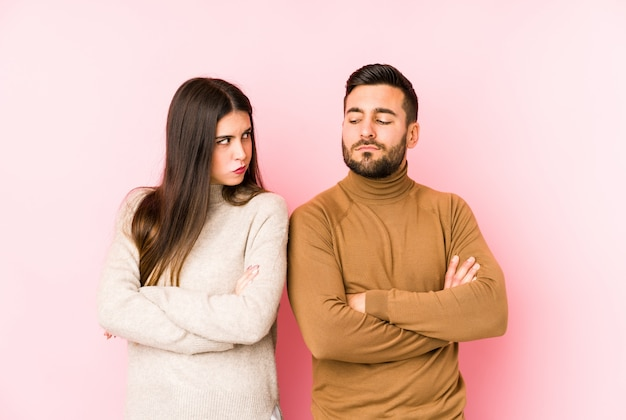 Young caucasian couple frowning face in displeasure, keeps arms folded.