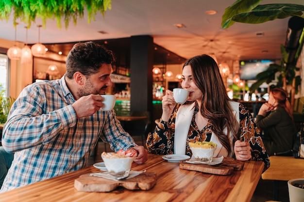 Молодая кавказская пара завтракает колумбийским кофе и смешанным фруктовым йогуртом для диеты в ресторане