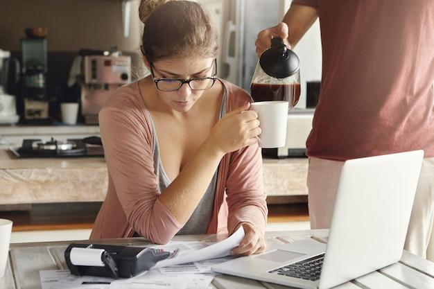 財政上の問題を抱えている若い白人カップル。家族の予算を管理しながらコーヒーを飲みながら、書類、ノートブックコンピューター、計算機を備えたキッチンテーブルに座っているメガネの女性を強調