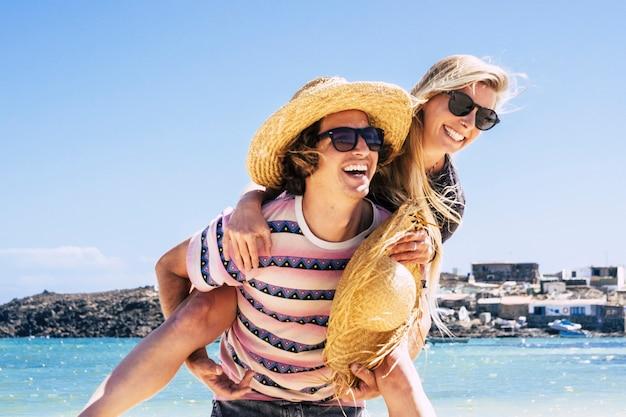夏休みの観光客が大好きなビーチで楽しんでいる若い白人カップル