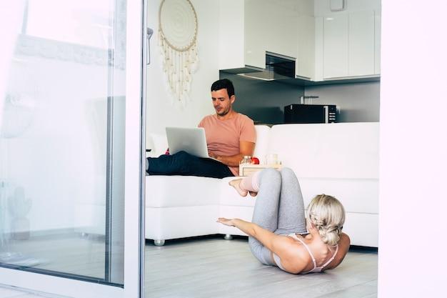 아름다운 집 안에 젊은 백인 부부는 랩톱 컴퓨터에서 작동하고 운동 피트니스 라이프 스타일을