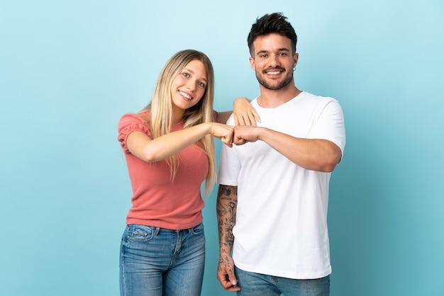 Молодая кавказская пара изолирована на синем фоне, ударяя кулаками