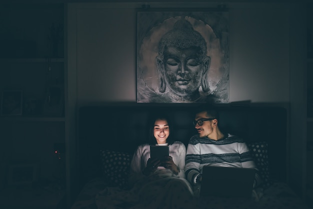 スマートフォンとコンピューターを使用してベッドに横たわっている若い白人カップル