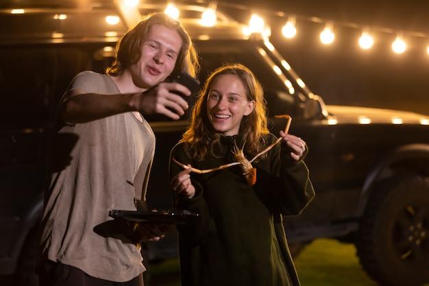 밤에 캠핑 저녁 파티에서 바베큐를 만드는 젊은 백인 부부. 남자와 여자 셀카