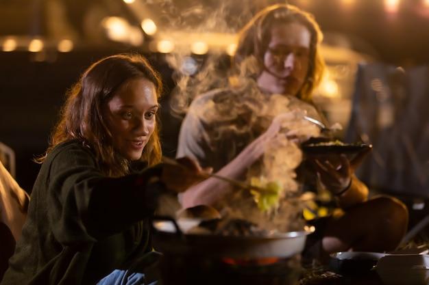 밤에 저녁 파티 캠핑에서 바베큐를 만드는 젊은 백인 부부