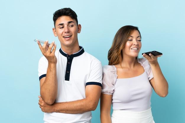 Молодая кавказская пара на синем, отправляя голосовое сообщение или электронную почту с мобильного телефона