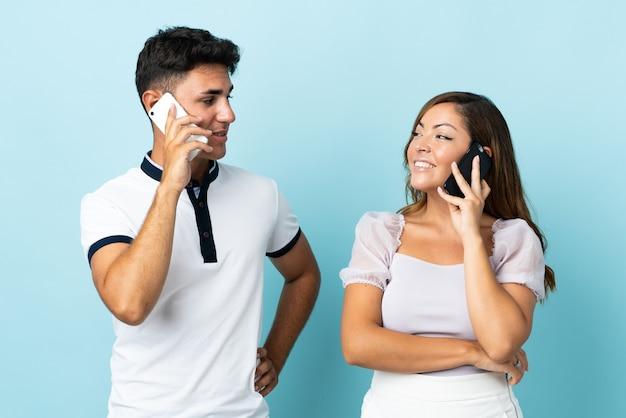 Молодая кавказская пара на синем разговаривает по мобильному телефону