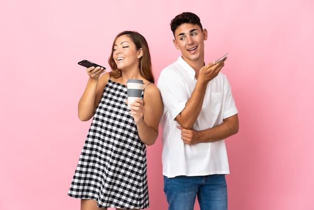 Молодая кавказская пара на розовом, отправляя голосовое сообщение или электронное письмо с мобильного телефона
