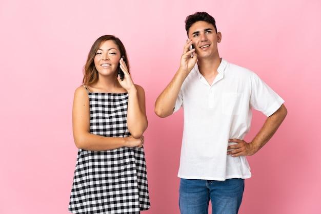 Молодая кавказская пара на розовом разговаривает по мобильному телефону