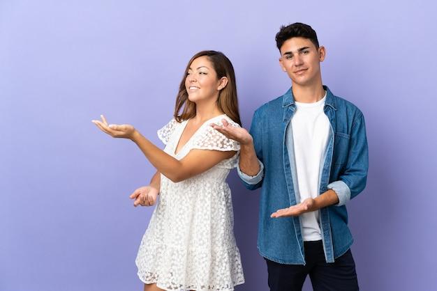 Молодая кавказская пара на фиолетовом, протягивая руки в сторону, приглашая прийти